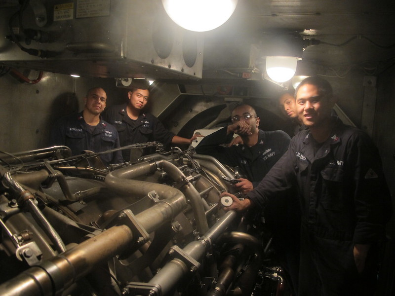 Sailors pose for a photo in the main engine room of USS Mobiel Bay