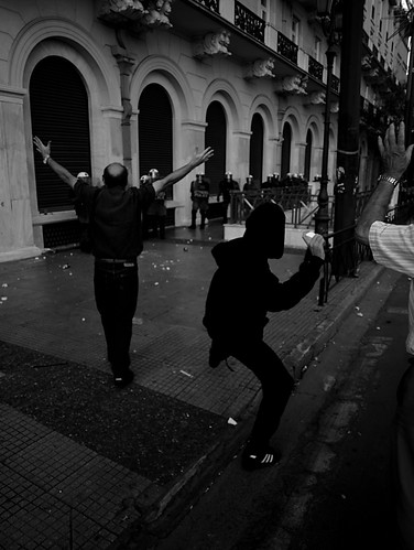 Greek youth throwing a rock at riot police units in Athens by Teacher Dude's BBQ