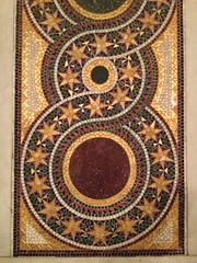 tapestry(0.0), floor(0.0), textile(0.0), prayer rug(0.0), flooring(0.0), art(1.0), pattern(1.0), mosaic(1.0), brown(1.0), design(1.0), circle(1.0), carpet(1.0),