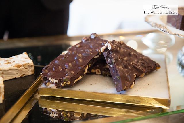 Chocolate bark with almonds, pistachio, hazelnuts on the dessert cart
