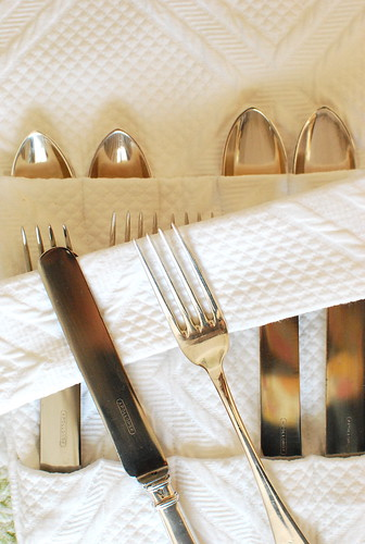 silver flatware in white cover