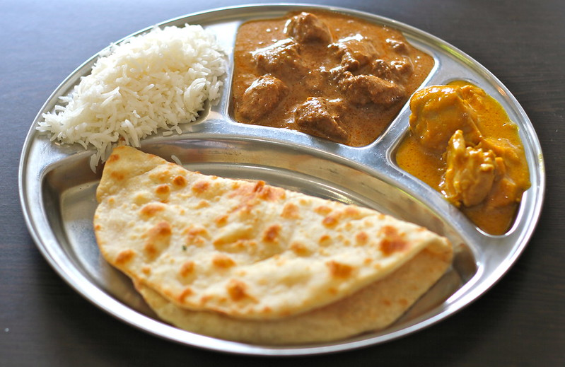 Two different curries with rice and naan