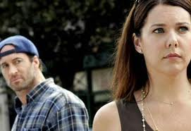 Lorelai is in the front right of the frame, walking away from Luke, who watches her. Both look pained.