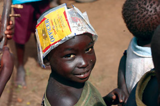 A child in Northern Uganda wears a hat fashioned  from trash lining the streets of a camp. Drinking is  rampant in the camps.