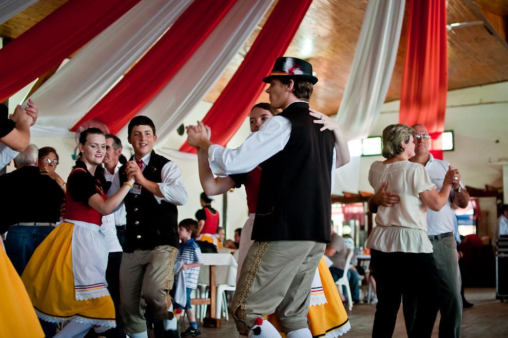 Miembros de la colectividad alemana de 25 de Mayo, que han visitado la Colonia Obligado desde Misiones Argentina, danzan con sus respectivas parejas en la parte central del club social, mientras el público presente disfruta del almuerzo del domingo 11 de Noviembre, la última fecha de la semana de la cerveza en dicha ciudad. (Elton Núñez)