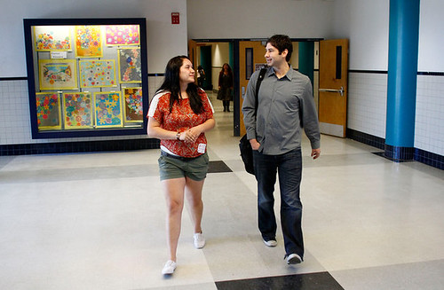 Image of Ana Verdugo walking with Matt de la Peña in a school hallway. Ana has long brown hair, is wearing a red t-shirt with green shorts. She's looking at Matt, who is wearing a grey button-down shirt and jeans.