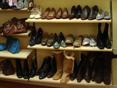 Three shelves of shoes/boots, with shoes on the upper shelves and ankle/knee boots on the lower ones.  Shelves to the side hold handbags.