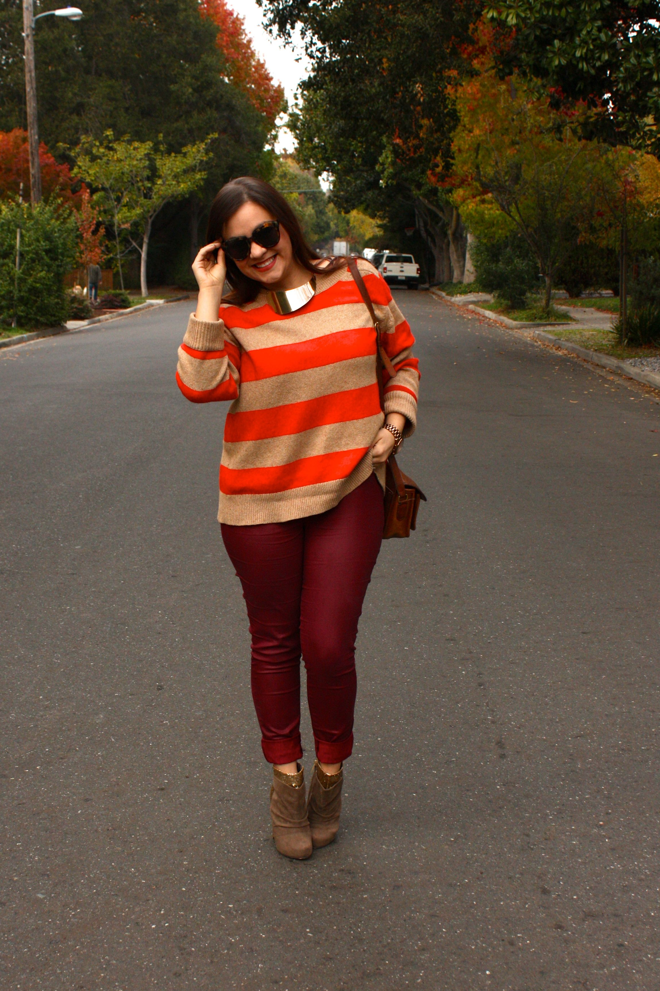 burgundy waxed jeans with orange striped lands end sweater and brown coach bag