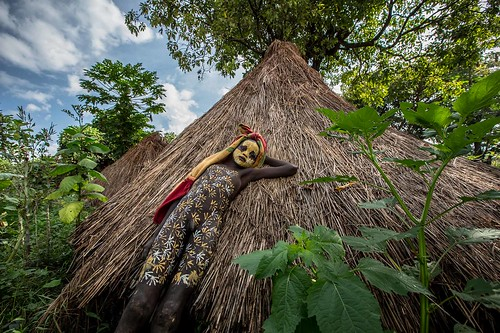Surma tribe boy with his face painted leaning against the hut