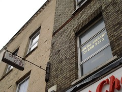 """An oblique view upwards onto the upper floors of a brick building. A window is visible with """"Dental Surgery / 01 688 5273"""" printed on it in gold lettering. A projecting sign reads """"Dental Surgery"""", though the """"s"""", """"u"""", """"r"""", and """"e"""" of """"surgery"""" are missing."""