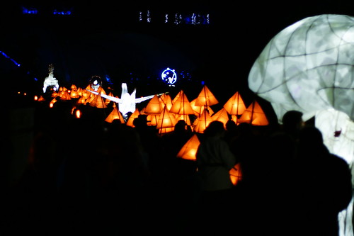 The parade. Large white lanterns resembling a tea party, an origami bird, a mushroom. In between the white lanterns, lots of yellow pyramid lanterns. The carriers cannot be seen except as occasional silhouettes