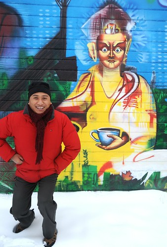 Lama Rabten Tshering kneels near Padmasambhava with coffee, Guru Rinpoche wall mural, Lama Rabten is a Spiritual Director of Nalandabodhi Foundation (Vancouver BC Canada), Lama G's Cafe, Fremont, Seattle, Washington, USA by Wonderlane