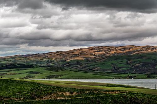 light lake green clouds gold hills nz otago