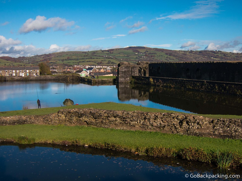 A man fishes on the artificial lake surrounding Caerphilly Castle