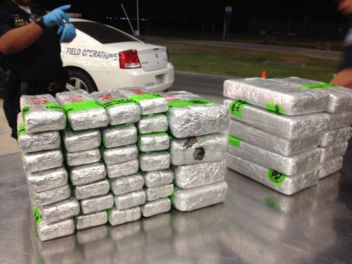 <p>A CBP officer does a final count of the bricks of heroin found in a small car.</p>