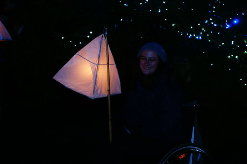 Mostly dark picture with pyramid lantern lit up. Me wrapped up in cold weather clothes and smiling. Some small twinkly lights in the background