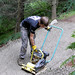 Sat, 07/28/2007 - 14:31 - On the 28th of July 2007 the Trailfairies descended on the Lombard Street section of Glentress's red route in order to repair a switchback corner that was showing signs of damage.  With drainage installed and the corner reshaped, Andy Wardman uses the wacker plate in order to produce a firm riding surface. Without this compaction the loose hardcore would quickly be eroded by rain and bike tyres.