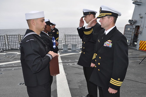 CO Commander Kurt M. Sellerberg accompanied by CMC Jeffrey A. Campbell, salutes the ashes of a fallen comrade