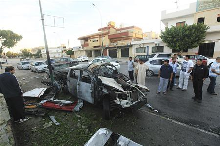 Crowd gathers around a car which exploded in Benghazi, Libya on November 4, 2012. The bomb was placed outside a police station. by Pan-African News Wire File Photos
