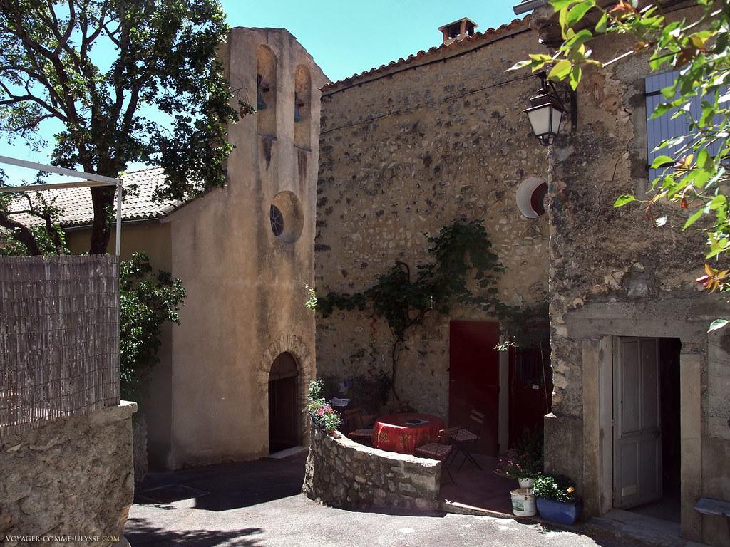 La façade de l'église, à demi cachée par les autres maisons du village, toutes proches. L'église fait partie de la paroisse de Sault de Vaucluse.