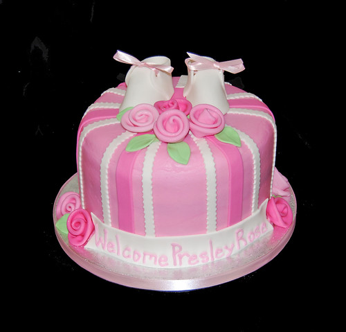 pink baby shower cake with roses and baby shoes