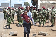 A man walks past the general service unit with his kid during the inter-ethnic riots in Kenya's Eastleigh suburb. Credit: Brian Ngugi/IPS