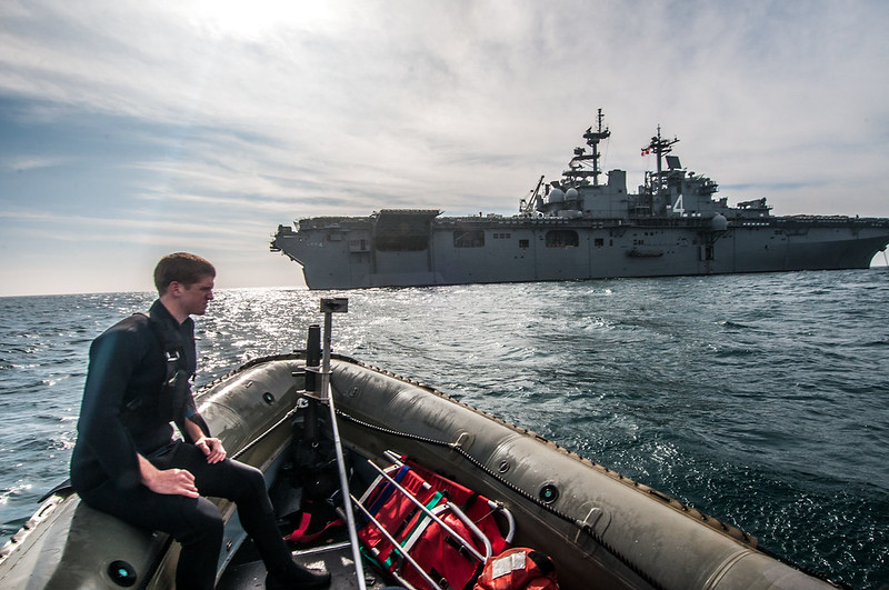 Search and rescue swimmer assigned to USS Boxer (LHD 4) stands watch aboard a 7-meter rigid hull inflatable boat