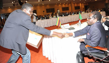 President Mugabe congratulates Zimbabwean journalist Kizito Sikuka of Sardc.net for winning the Comesa Media Award in Uganda on November 22, 2012. — (Picture by Presidential photographer Joseph Nyadzayo) by Pan-African News Wire File Photos