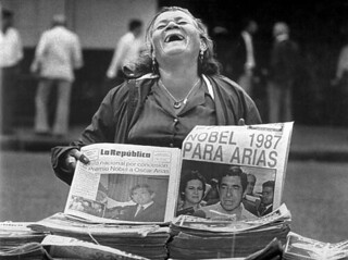 A Costa Rican newspaper vendor is overjoyed that  Dr. Oscar Arias, a Latin American leader, received  the Nobel Peace Prize in 1987.