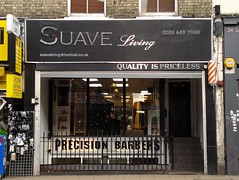 "A terraced shopfront with steps leading up to a mezzanine at ground level and railings separating off another shopfront in the basement. The ground floor shop has a sign reading ""Suave Living / 0208 649 7988 / suaveliving@hotmail.co.uk / Quality is priceless"" and the basement shop has a sign reading ""Precision Barbers""."