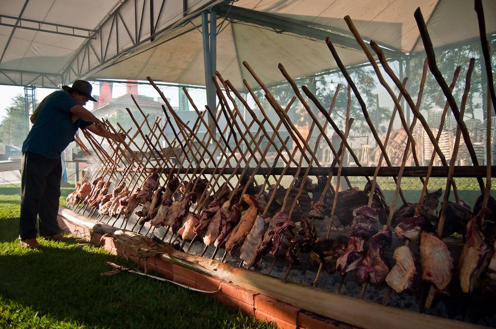 Un encargado atiende las carnes que se están asando a la estaca durante la preparación de las comidas que se consumirían en la noche del 3 de Noviembre en el Chopp Fest de Colonia Independencia. (Elton Núñez)