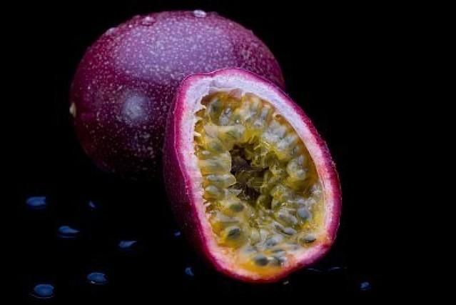 8110604-entera-y-en-rodajas-fruta-de-la-pasion-sobre-fondo-negro-con-gotitas-de-agua