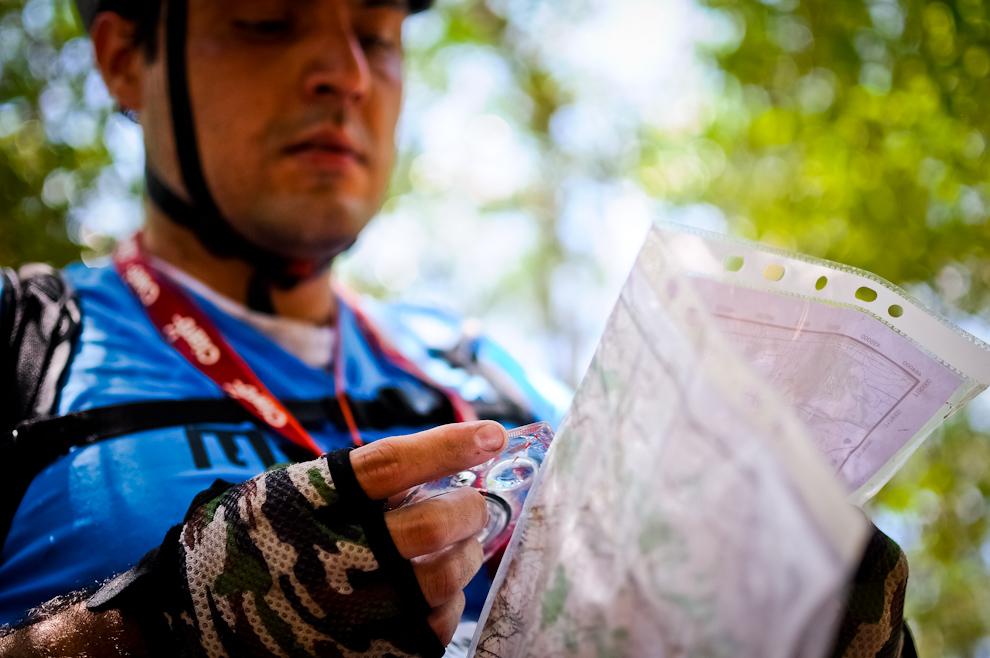 """Un participante de la categoria """"MB"""" (mountain bike) se detiene para analizar su ubicación y determinar su próximo rumbo, utilizando mapa y brújula, herramientas indispensables para terminar esta carrera. (Elton Núñez)"""