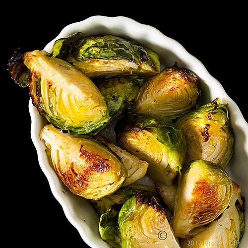 Roast Brussels Sprouts in Oblong Ramekin, Overhead View on Black