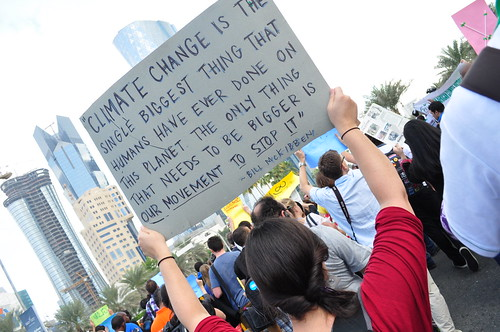 Protester holds up a placard at Qatar's first ever rally against climate change
