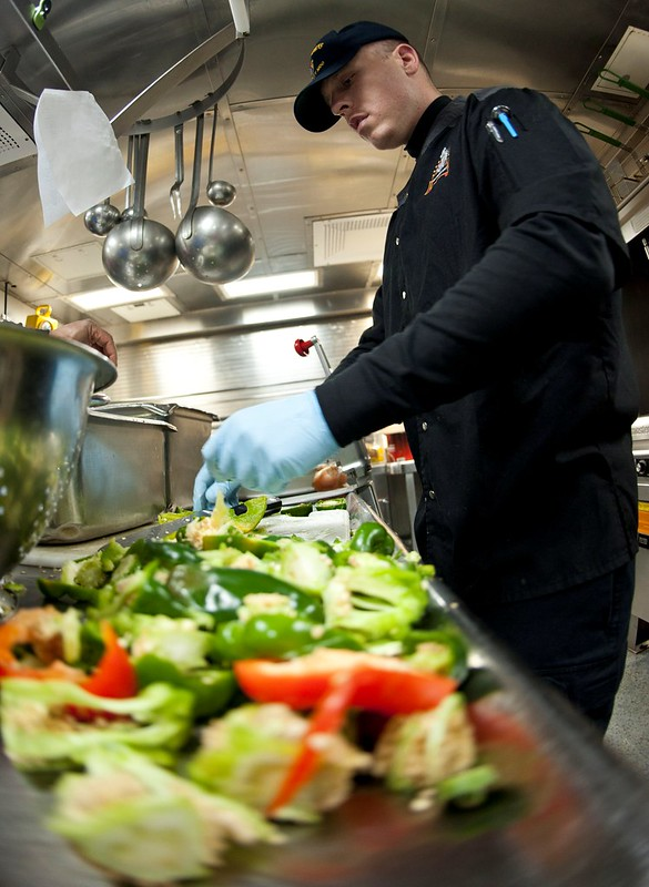 Culinary Specialist Seaman Apprentice Kyle Woolf prepares peppers for dinner on board USS Cowpens