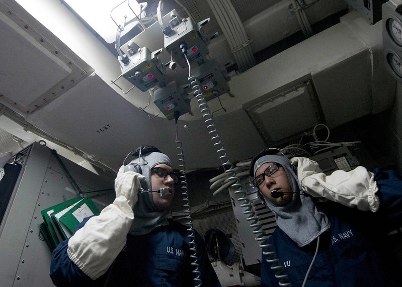 Sailors perform a communications check in one of the repair lockers.