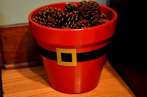 Painted Santa planter filled with pine cones