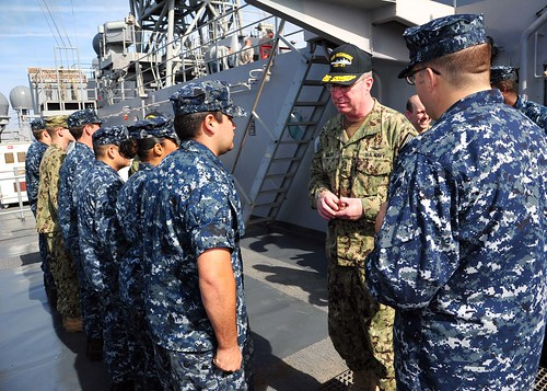 Vice Adm. John W. Miller presents coins to Sailors