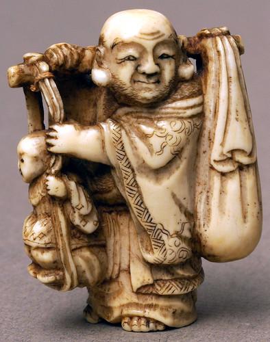 006-Netsuke de Marfil representa a un hombre que lleva una rama sobre sus hombros con un saco atado a un extremo y un niño-Bolton Museum and Archive Service