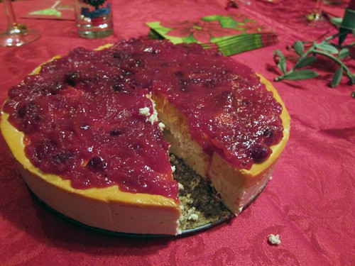 A tall, multi-layer cheesecake topped with cranberry sauce.