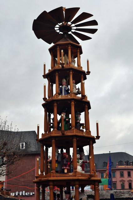 La pirámide navideña, conocida en Alemania como Höfchen, tiene once metros de altura. La pirámide consta de cinco niveles. Además de las figuras típicas de navidad, son típicas las figuras de personajes relevantes de Mainz. En el primer nivel: La Stecher Schoppe , un jugador de fútbol de Mainz 05, un corredor de Maratón y un rotor de Gutenberg. En el segundo nivel, tercer y quinto, como protagonistas son el invierno y los personajes típicos de Navidad (muñecos de nieve, Santa, ...). El cuarto nivel incluye personajes ilustres de Mainz: - El inventor de la imprenta Johannes Gutenberg con la Biblia de Gutenberg en la mano - El arquitecto de la ciudad Edward Kreyssig con un modelo de la Iglesia de Cristo en la mano. - El Bajazz con la linterna (Pagliacci y Carnaval Mainz) - Bishop (diócesis de Mainz) - La ciudad romana de la diosa Moguntia (Mogontiacum) de donde viene el nombre de la Ciudad. Mercado navideño de Mainz, uno de los más bonitos de Alemania - 8295326016 7104f0da69 z - Mercado navideño de Mainz, uno de los más bonitos de Alemania
