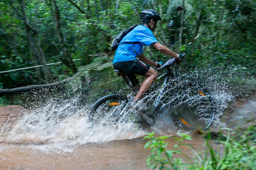 Cruzando el arroyo a gran velocidad con su bicicleta, un competidor avanza hasta el siguiente puesto de control. (Tetsu Espósito)