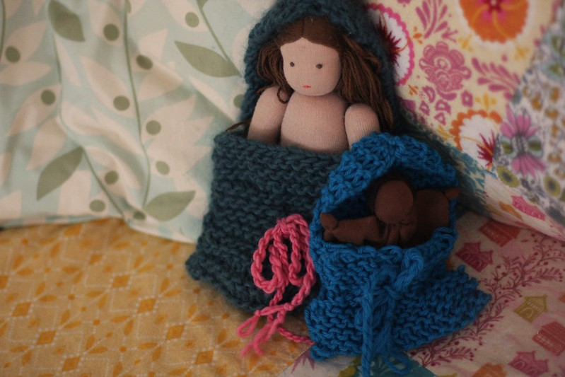 K's knitted baby sacks for C's doll (back) and her own doll (front)