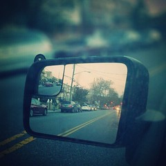 glasses(0.0), fisheye lens(0.0), darkness(0.0), sunglasses(0.0), driving(1.0), automotive mirror(1.0), window(1.0), vehicle(1.0), sunlight(1.0), rear-view mirror(1.0), light(1.0), glass(1.0), reflection(1.0), morning(1.0), blue(1.0),