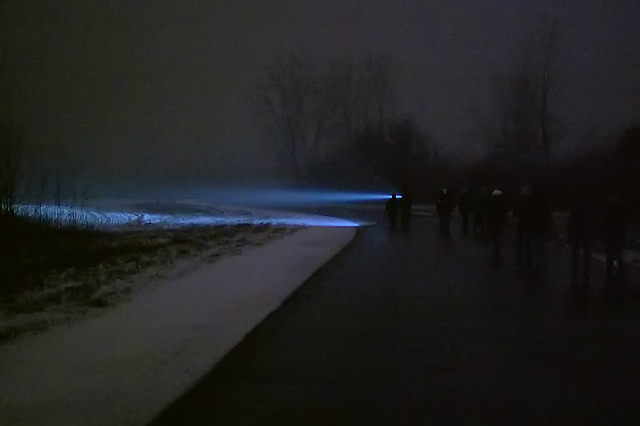 Columbia Bottom Conservation Area, in Saint Louis County, Missouri, USA - hikers in forest at night in the snow and fog with flashlight beam