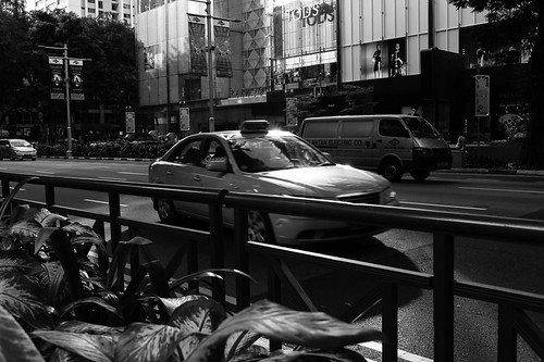 Evening sun glinting off a cab zooming down Orchard Road
