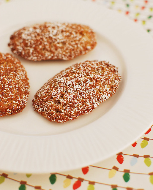 three Gingerbread Madeleins dusted with powdered sugar on a white plate