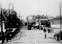 A black-and-white photo showing a view up a wide street with tram tracks running along it. An old-style tram is visible in the middle of the photo. Buildings of various architectural styles line both sides of the street. In the foreground, the street runs over a bridge open on both sides. A number of pedestrians are walking along the pavements, and one is crossing the road.