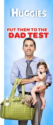 Thin vertical banner with blue background. Man in a suit holds a baby and a changing bag in each hand, and looks pained/goofy. A caption reads: Huggies. Put them to the dad test.